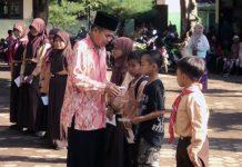 Drs Mujiman M.MPd Kepala Sekolah SDN Ambulu I saat memberikan santunan pada siswa yatim dan piatu