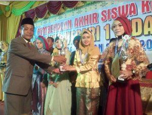 Kepala Sekolah, Drs Ahsan MM saat menyerahkan tropi dan piagam ke para lulusan terbaik SMPN 1 Sidayu.